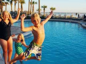 Kids posing for camera by pool photo