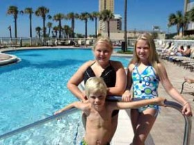 3 Kids pose for camera by pool photo